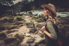 Frauenwanderer, der nahe wildem Gebirgsfluss geht Stockfoto