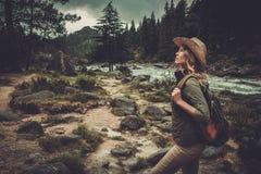 Frauenwanderer, der nahe wildem Gebirgsfluss geht Stockbilder