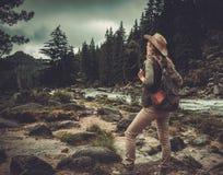 Frauenwanderer, der nahe wildem Gebirgsfluss steht Stockbilder