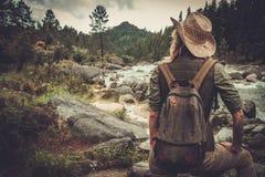 Frauenwanderer, der nahe wildem Gebirgsfluss steht Stockfotos