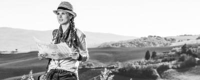 Frauenwanderer, der in Toskana mit der Karte untersucht Abstand wandert Lizenzfreie Stockfotografie
