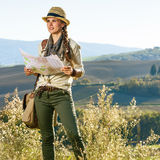 Frauenwanderer, der in Toskana mit der Karte untersucht Abstand wandert Stockfotografie