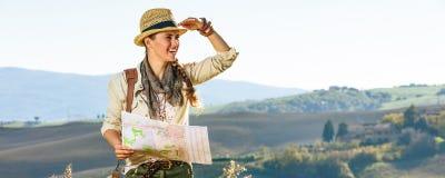 Frauenwanderer, der in Toskana mit der Karte untersucht Abstand wandert Stockbild