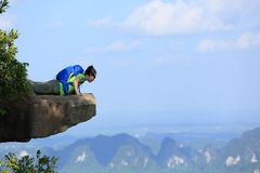 Frauenwanderer, der unten auf Bergspitzeklippe schaut lizenzfreie stockbilder