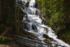 Frauenwanderer, der Wasserfall betrachtet stockfoto