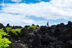 Frauenwanderer geht auf das scharfe vulkanische Land stockbilder