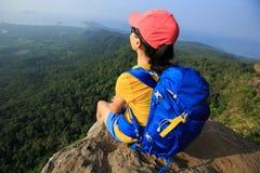 Frauenwanderer genießen die Ansicht, die auf Bergspitze wandert Stockfotografie
