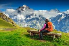 Frauenwanderer mit dem Rucksack, der auf der Bank sich entspannt Stockbilder