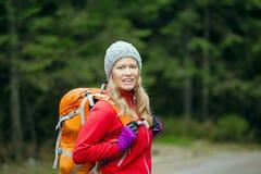 Frauenwanderer mit dem Rucksack, der im Wald wandert Stockbild