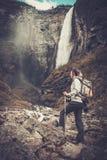 Frauenwanderer mit dem Rucksack, der nahe Vettisfossen-Wasserfall steht Lizenzfreie Stockfotos