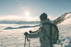 Frauenwanderer mit den Wanderstöcken, welche die Ansicht hoch oben auf den Alpen betrachten Hintere Ansicht, kalter Schnee des Wi lizenzfreies stockbild