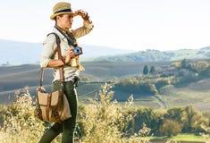 Frauenwanderer mit der Weinlesefotokamera, die den Abstand untersucht Lizenzfreie Stockbilder