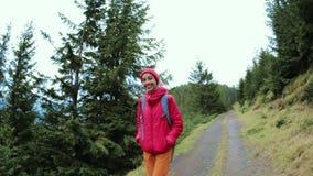 Frauenwanderer mit Rucksack, tragend in der roten Jacke und orange in den Hosen und gehen auf den Gebirgshintergrund stock video