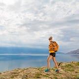 Frauenwanderer mit Rucksack, wandernd an der Küste und an den Bergen Stockbilder