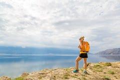 Frauenwanderer mit Rucksack, wandernd an der Küste und an den Bergen Stockbild