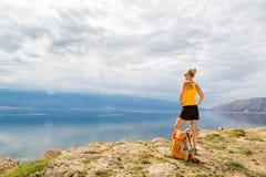 Frauenwanderer mit Rucksack, wandernd an der Küste und an den Bergen Stockfotos
