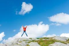 Frauenwanderer springt auf Steine Stockfotografie