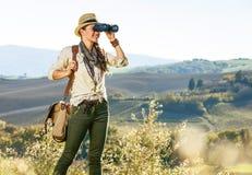 Frauenwanderer in Toskana, die Abstand durch Ferngläser untersucht Stockfotos