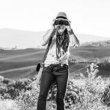 Frauenwanderer in Toskana, die in camera durch Ferngläser schaut Stockfotografie