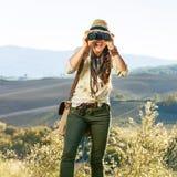 Frauenwanderer in Toskana, die in camera durch Ferngläser schaut Lizenzfreie Stockbilder