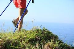 Frauenwandererbeine, die auf Küstenberg wandern Lizenzfreie Stockbilder