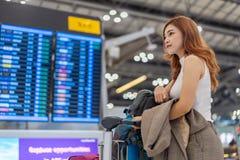 Frauenwarteflug mit Informationsbrett im Flughafen lizenzfreie stockfotos