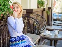 Frauenwartezeitdatum Kreative grafische Mitteilung für Ihr Design Mädchen sitzen Caféatemzug-Blumenaroma Schöne Terrasse ziehen K stockfotos