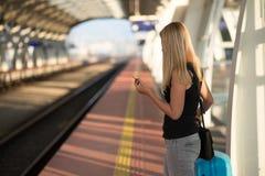 Frauenwartezug auf Bahnstationsplattform lizenzfreies stockfoto
