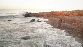 Frauenweg am Strand bei Sonnenuntergang stock footage