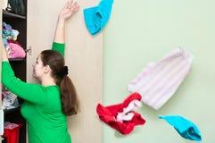 Frauenwerfen Kleidung von der Garderobe Lizenzfreie Stockfotografie