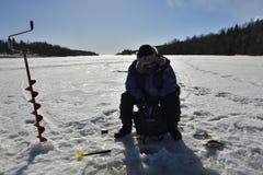 Frauenwinterfischen auf dem Eis Stockfoto