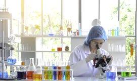 Frauenwissenschaftler, der Experiment mit Mikroskop tut stockbild