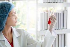 Frauenwissenschaftler oder -chemiker, die rote flüssige Substanz im Reagenzglas überprüfen lizenzfreie stockbilder