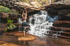 Frauenyoga asana an der Wasserfalleinstellung stockfotos