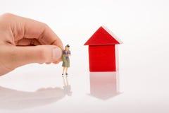 Frauenzahl in der Nähe ein Haus gemacht von den Blöcken Lizenzfreie Stockfotografie