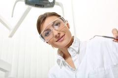 Frauenzahnarzt in den Schutzgläsern mit Spiegel Lizenzfreies Stockfoto