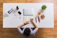 Frauenzeichnung im Büro des Notizbuches zu Hause Stockfotografie