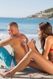 Frauenzeichnungs-Herzmuster mit Sonnencreme auf ihrem Freund-BAC Lizenzfreie Stockbilder