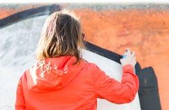 Frauenzeichnungsgraffiti mit Sprühfarbe von der Rückseite Lizenzfreie Stockfotos