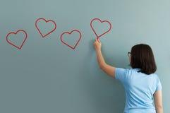 Frauenzeichnungsherz für Valentinsgrußtag mit roter Kreide auf Wand Stockfotografie