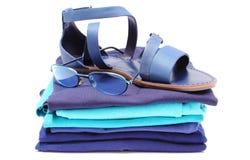 Frauliche Sandalen und Sonnenbrille auf Stapel der blauen Kleidung Weißer Hintergrund Stockfoto
