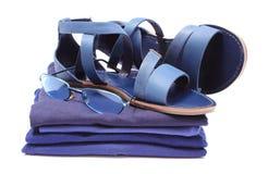 Frauliche Sandalen und Sonnenbrille auf Stapel der blauen Kleidung Weißer Hintergrund Lizenzfreie Stockfotos
