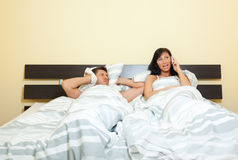 Frautelefon im Bett mit frustriertem Ehemann Stockfoto
