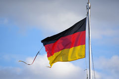 Frayed flag of Germany fluttering in the wind against a blue sky Stock Image