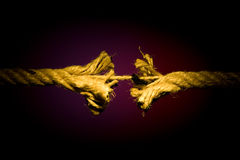 Frayed rope breaking. On a dark background royalty free stock photos