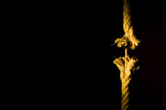 Frayed rope breaking. On a dark background stock photos