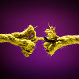 Frayed rope breaking. On a dark background royalty free stock photo