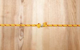 Frayed rope at breaking point. On wooden background stock image