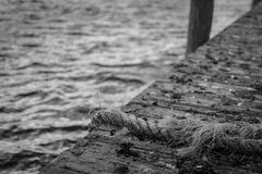 Frayed rope on dock. A frayed rope hanging off the edge of a dock royalty free stock photo