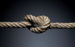 Frayed rope knot. On a dark background stock photo